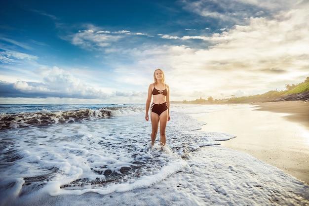 Девушка в черном купальнике гуляет по океану