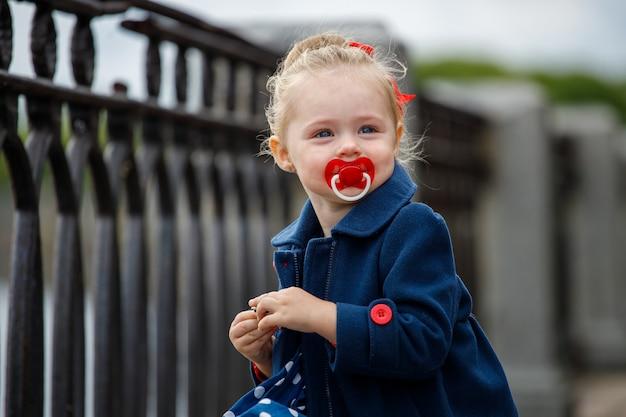 通りで彼女の口におしゃぶりを持つ青いコートを着た女の子