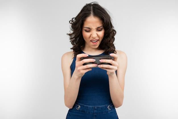 파란 드레스에 여자 복사 공간이 회색 스튜디오에 가로 위치에 스마트 폰을 보유하고