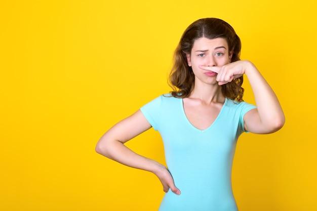 青いドレスを着た女の子は、人差し指で鼻の下の口ひげを模倣します