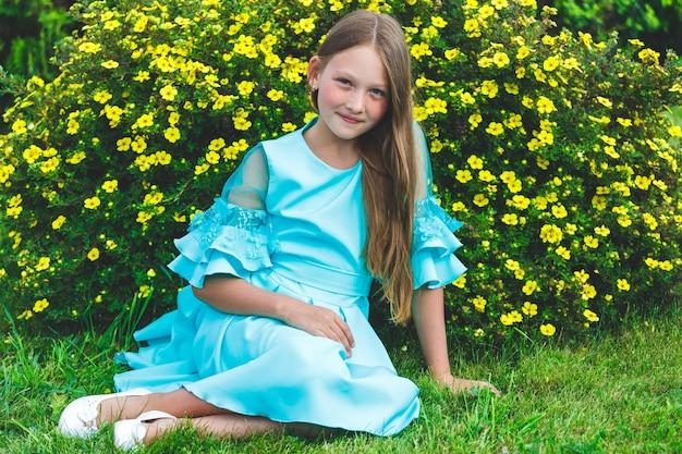 青いドレスを着た女の子が公園の芝生の上に座っています