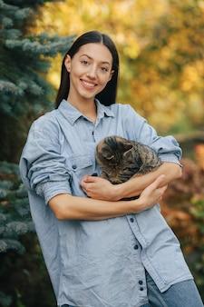 Девушка в синей рубашке стоит на фоне деревьев