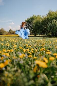 파란색 실크 드레스를 입은 소녀는 여름과 청소년 알레르기가 없는 개념의 바람에 드레스를 개발하는 노란 민들레가 있는 녹색 들판에서 뛰고 있습니다.
