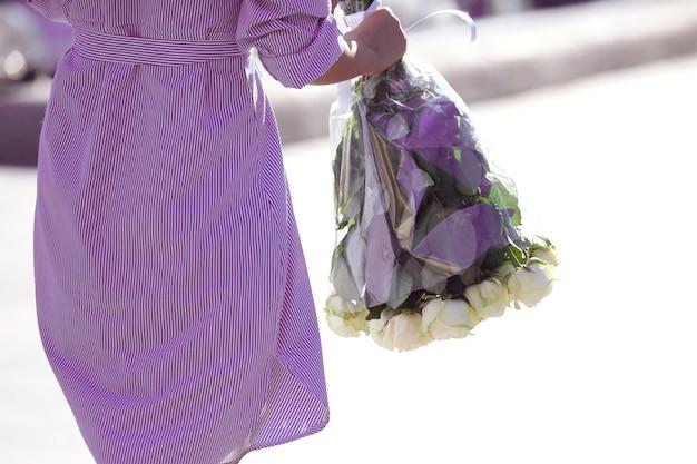 파란색 줄무늬 드레스를 입은 소녀는 흰 장미 꽃다발과 함께 제공됩니다. 사랑과 가족 관계
