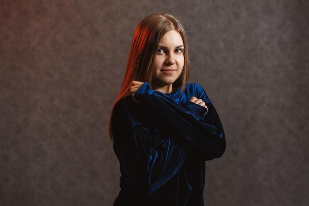 Девушка в синем свитере на сером фоне. у нее красивые волосы, и она красиво позирует