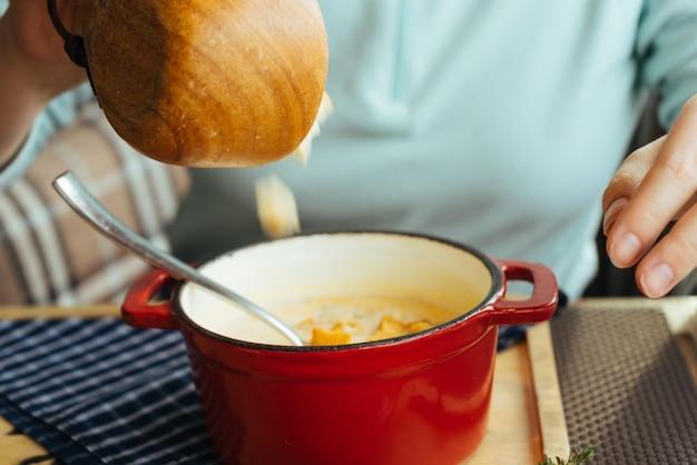 熱い芳香のスープとカフェで青いスウェットシャツの女の子