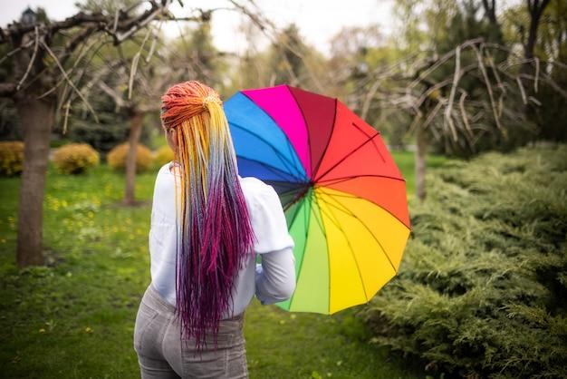 明るい化粧と長い色の三つ編みの青みがかったシャツの女の子。傘をさして