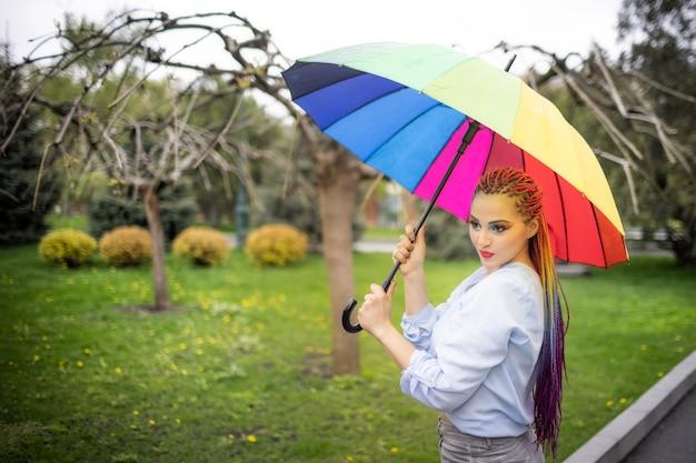 明るい化粧と長い色の三つ編みの青みがかったシャツの女の子。笑顔と傘を持って