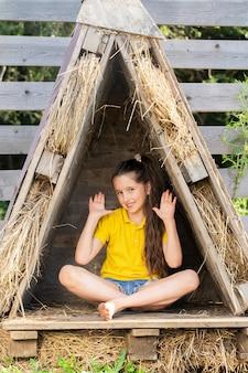 Девушка в ярко-желтой футболке сидит в маленькой хижине