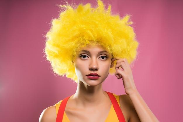 밝은 노란색 가발을 쓴 소녀는 분홍색 배경에 격리된 카메라를 쳐다본다