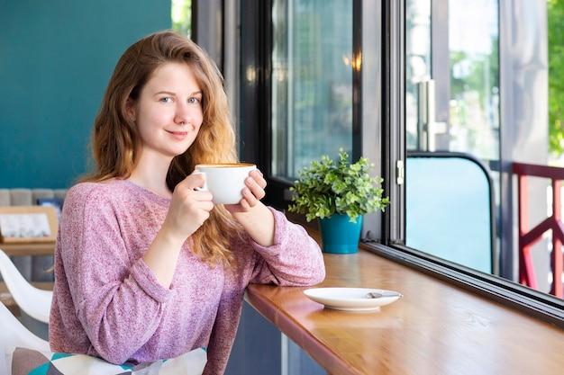 커피 한잔과 함께 카페에서 소녀 미소하고 라떼를 마시는.