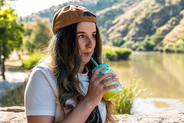 녹색 유리에 주스를 마시는 모자에 소녀. 강변. 라이프 스타일 컨셉