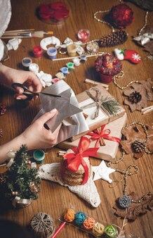 Девушка в клетчатой рубашке и новогодней шапке разрезает сияющую звезду
