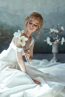 床に座っているシックなロングドレスの女の子。花嫁の体に白いウェディングドレス。長い裾の美しいライトドレス、結婚式前の壊れやすい繊細な女の子の肖像画