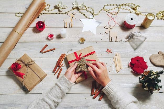Девушка в уютном вязаном свитере, украшенном новогодней подарочной коробкой