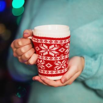 赤いニットのマグカップからコーヒーを飲みながら居心地の良いニットセーターの女の子