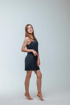 회색 배경에 포즈 검은 드레스 소녀