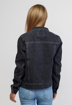 흰색 바탕에 데님 블랙 재킷과 블루 데님 바지를 입은 소녀.