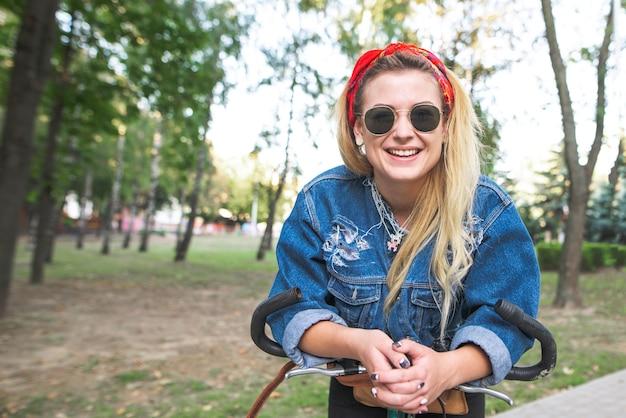 デニムジャケットの女の子とカメラを見て、笑みを浮かべて自転車公園でサングラスの視力