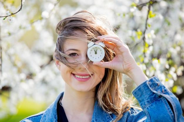 公園の開花の木の近くに、デニムジャケットと目覚まし時計を着た女の子が立っています。春の季節