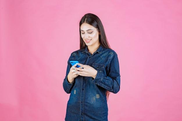 그녀의 스마트 폰에서 채팅 데님 셔츠에 소녀