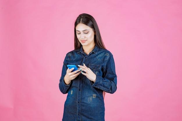 Девушка в джинсовой рубашке болтает на своем смартфоне