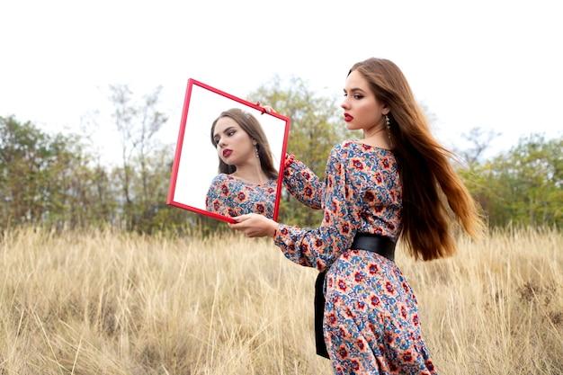 Девушка в платье в цветах с зеркалом