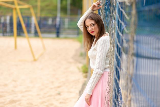 Девушка в платье на поле для пляжного футбола. фото высокого качества