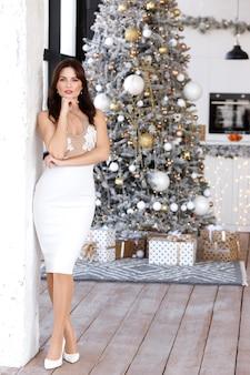새해에 크리스마스 트리에서 우아한 흰색 드레스 소녀