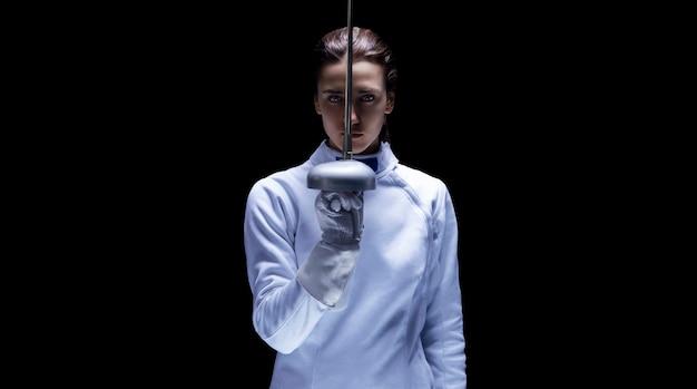 그녀의 손에 칼을 들고 포즈를 취하는 검객 의상 소녀