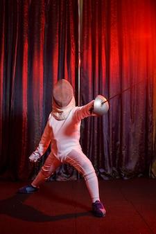 剣を手に、ネオンの光でフェンシングの衣装を着た女の子。若い鉄道模型は、動き、行動を訓練します。スポーツ、若者、健康的なライフスタイル。