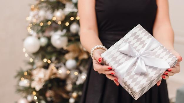 Bokeh와 크리스마스 트리의 축제 검은 드레스에 여자는 선물을 보유