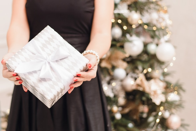 Bokeh와 크리스마스 트리 배경에 축제 검은 드레스에 여자는 선물을 보유하고