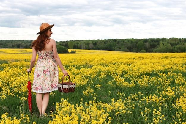 Девушка в поле цветов с зонтиком и шляпой