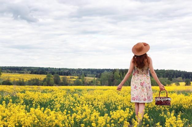 Девушка в поле цветов с корзиной и шляпой