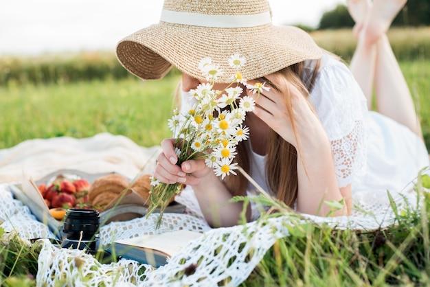 ヒナギクの畑の女の子、村の夏。屋外でリラックスしてピクニックをしている若い笑顔の女性、彼女は草の上の毛布の上に横たわっています
