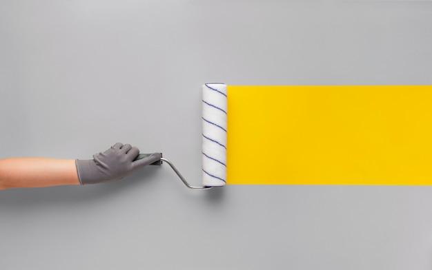 장갑 입은 소녀는 회색 벽에 롤러로 노란색 스트립을 그립니다. 창의적인 혁신 개념.