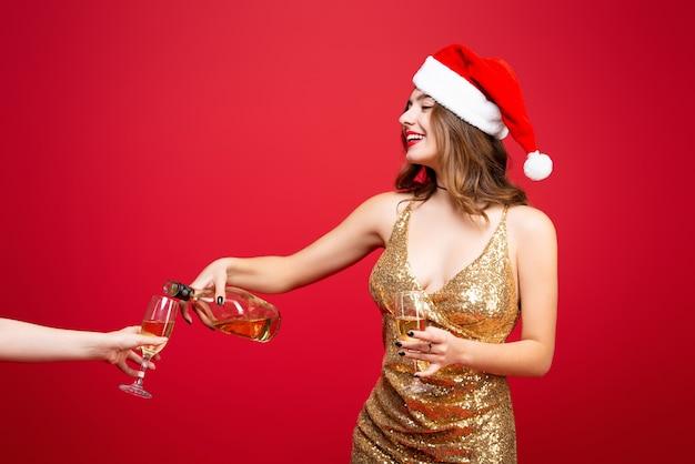 金のドレスとクリスマスの帽子の少女は赤でシャンパンを飲みます