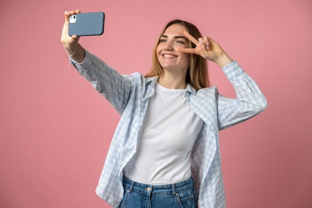 機嫌の良い女の子がピンクで隔離された電話で自分撮りをします
