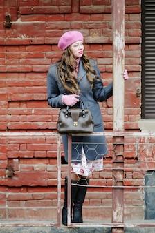 旧市街の通りに灰色のコートとピンクのベレー帽の女の子