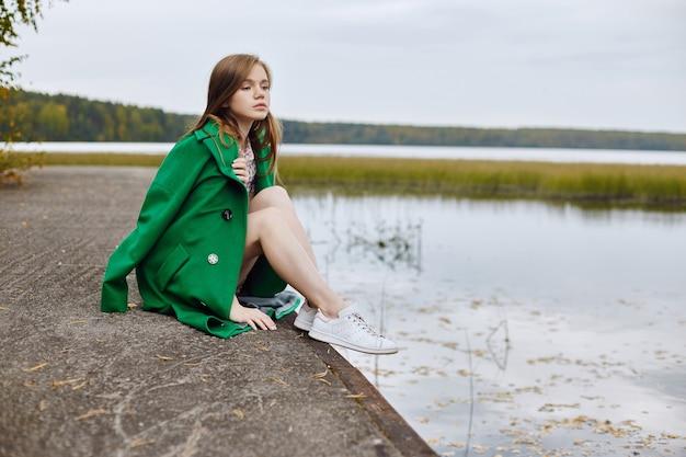 녹색 코트를 입은 소녀가 흐린 가을 날 호수 제방을 따라 걷습니다. 가을 패션과 의류, 물에 떠 있는 노란색 낙엽. 로맨틱 무드