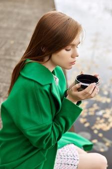Девушка в зеленом пальто гуляет по набережной озера в пасмурный осенний день. осенняя мода и одежда, желтые опавшие листья, плавающие в воде. романтическое настроение