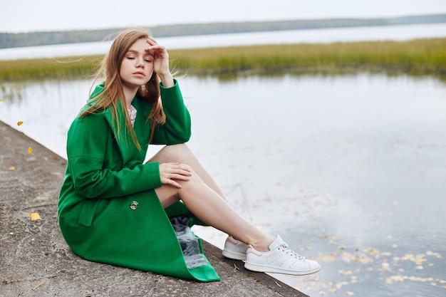 녹색 코트를 입은 소녀는 흐린가 날에 호수 제방을 따라 산책합니다. 가을 패션과 의류, 물에 떠 다니는 노란 낙엽