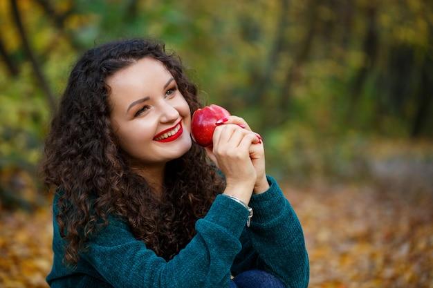 가을 숲에서 녹색 스웨터와 사과를 손에 든 소녀