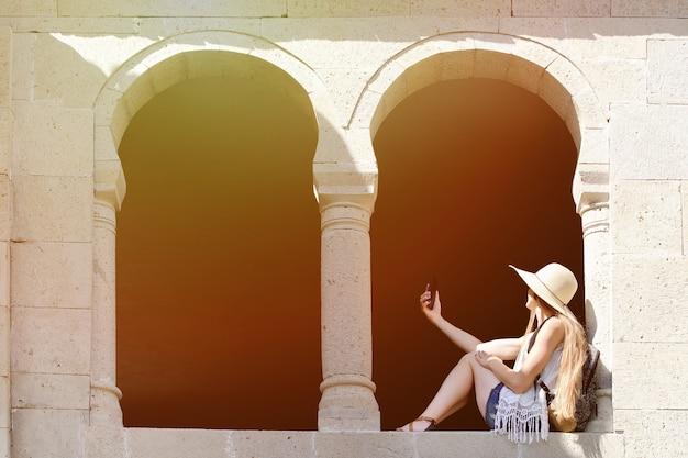 Девушка в шляпе и с рюкзаком сидит в арке старого окна делает селфи