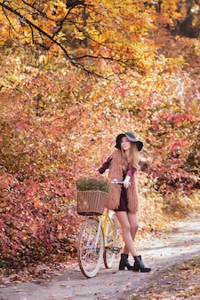 帽子と散歩に黄色の秋の自転車の女の子。