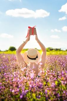 Девушка в шляпе держит подарок с красной лентой в руках. виктория кракка летом в поле. цветы цветут. концепция праздника, натуральные подарки.
