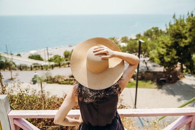 Девушка в шляпе смотрит на турецкий морской пейзаж анталии летом, путешествуя по турции, отдыхая, наслаждаясь ...