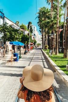 Девушка в шляпе смотрит на турецкую улицу анталии во время летнего путешествия в турцию, отдыхая, наслаждаясь ... Premium Фотографии