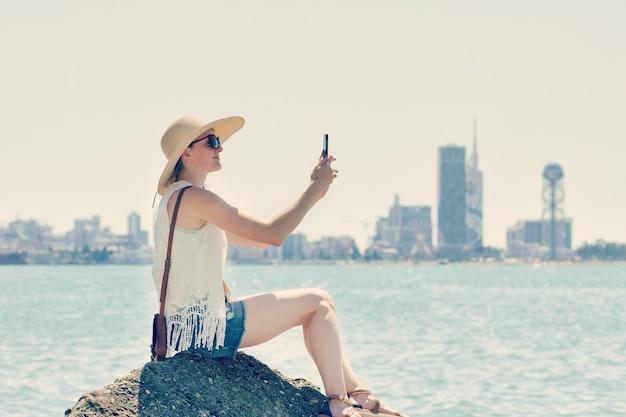 Девушка в шляпе делает селфи, сидя на скале у моря